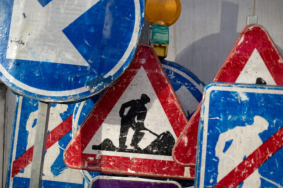 Mixture of construction signs including colours of clue red and white. Centre image is silhouette of a man digging dirt